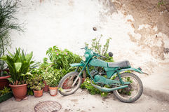 Old motorbike parked against a rustic wall. Old green motorbike parked against a rustic wall of a house with potted plants in Andalusia in Spain, copyspace on Royalty Free Stock Photography