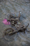 Old motorcycle buried in the sludge with pink plastic bag Stock Photos