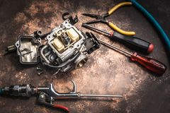 Old motorcycle carburettor and tools on Rusty table .  Be prepar. Ed to clean up Stock Photos