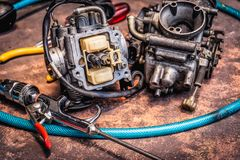 Old motorcycle carburettor and tools on Rusty table .  Be prepar. Ed to clean up Stock Photography