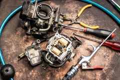 Old motorcycle carburettor and tools on Rusty table . Be prepar royalty free stock photos