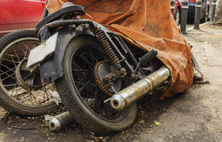 Old motorcycle covered with canvas Stock Images