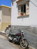 Old motorcycle in front of the house. On the street Royalty Free Stock Photo