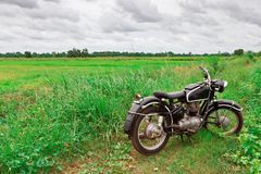 Old Motorcycle in Meadow Stock Images