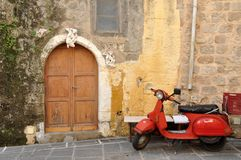Old motorcycle by a greek house in Rhodes, Greece. Old motorcycle by an orange warm greek house in Rhodes, Greece Royalty Free Stock Photography