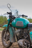 An old motorcycle - partial view of front part with  dirty tank with smudges of gasoline and handlebar on off-road Stock Photography