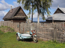 Old motorcycle with sidecar near fence. Countryside. Russia. View of traditional village house with wooden fence. Old motorcycle with sidecar. Blue sky, clouds Royalty Free Stock Photo