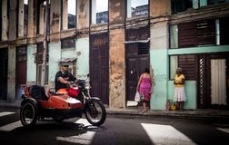 Old motorcycle with sidecar. Passing chatting women in havana vieja Royalty Free Stock Image