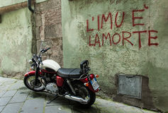 Old motorcycle standing in front of a wall with the writing  Stock Image