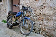 Old motorcycle standing at a wall. Very old motorcycle standing at a wall Royalty Free Stock Image