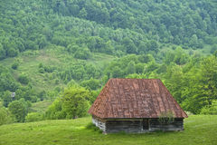 Old mountain countryside house - Romania. Old Romanian mountain countryside house and the green surroundings around it Royalty Free Stock Photography