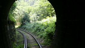 Old mountain train tunnel 3. Back view of railroad train that entering a dark and old mountain tunnel. Inaugurated in 1863, it is the oldest mountain railway in stock footage