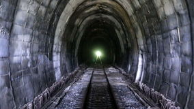 Old mountain train tunnel 4. Back view of railroad train that entering a dark and old mountain tunnel. Inaugurated in 1863, it is the oldest mountain railway in stock video footage