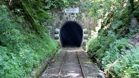 Old mountain train tunnel 5. Back view of railroad train that entering a dark and old mountain tunnel. Inaugurated in 1863, it is the oldest mountain railway in stock video
