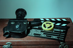 Old movie camera clapper and reel with a film Royalty Free Stock Image