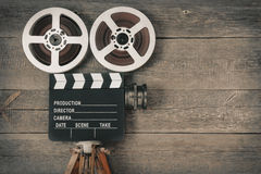 Old movie camera. Consisting of a tripod, lens, film reels and clapperboards Royalty Free Stock Images