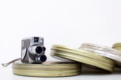 Old movie camera and film canisters on white royalty free stock photography