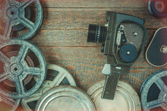 Old movie camera and film reel. Lying on a wooden table.Film effect from the illuminated edges royalty free stock photography