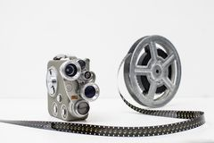 Old movie camera with film reel on white background Stock Photos