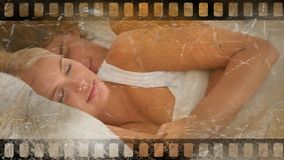 Old Movie tape video. Old Movie tape showing happy cupple laying in bed stock video footage