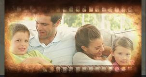 Old Movie tape video. Old Movie tape showing happy family sitting on sofa stock footage
