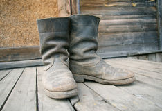 Old muddy farmers boots Stock Photo