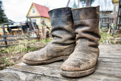 Old muddy farmers boots Royalty Free Stock Image