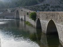 Old multi arched stone bridge on Ceyhan River stock photography