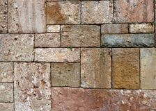 Old multicolor stone block wall. Old stone block monastery wall with different shapes colors and textures Royalty Free Stock Photos
