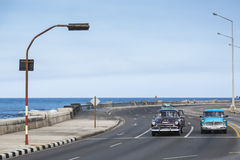 OLD MUSCLE CARS WAITING OVER HAVANA BREAKWATER Royalty Free Stock Photography