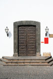 Old Museum Doors. Beautifully carved wooden doors to a monastry, now a museum. Shaped lava rock surround and an old cardboard box of stuff on the doorstep stock photo