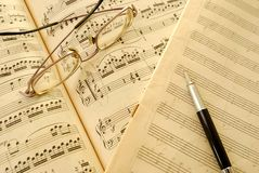 Old music score, manuscript and pen. Music score, manuscript and pen with sepia effect to signify aging and wear and tear. For concepts such as music composition Royalty Free Stock Image
