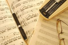 Old music score, manuscript and pen. Music score, manuscript, metronome, glasses and pen with sepia effect to signify aging and wear and tear. For concepts such Stock Image