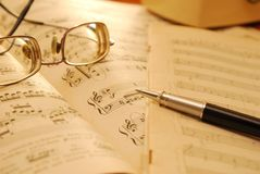 Old music score, manuscript and pen. Music score, manuscript and pen with sepia effect to signify aging and wear and tear. For concepts such as music composition Stock Images