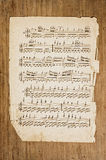 Old musical page. Old musical score page on wooden surface Royalty Free Stock Photography