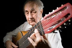 Old musician. An elderly man in white shirt playing an acoustic guitar. Dark background Stock Photo