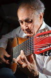 Old musician. An elderly man in white shirt playing an acoustic guitar. Dark background. Focus on the hand Stock Image