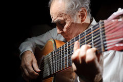 Old musician. An elderly man in white shirt playing an acoustic guitar. Dark background Stock Photos