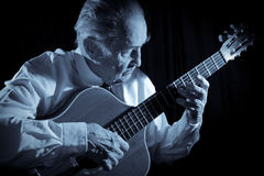 Old musician. An elderly man in white shirt playing an acoustic guitar. Dark background. Monochrome Stock Image