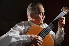 Old musician. An elderly man in white shirt playing an acoustic guitar. Dark background Royalty Free Stock Photo