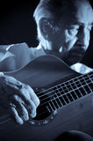 Old musician. An elderly man in white shirt playing an acoustic guitar. Dark background. Monochrome.  Focus on the hand Royalty Free Stock Photography