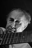 Old musician. An elderly man in white shirt playing an acoustic guitar. Dark background. Monochrome Stock Photos