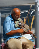 Old musician playing the violin. An elderly man sits by the roadside and plays on the old violin. Sudak, Crimea, summer 2014 Royalty Free Stock Images