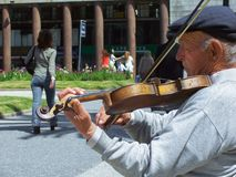 This old musician is always playing the violin to brighten the independence plaza royalty free stock image