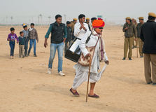 Old musician in sunglasses with a keyboard in a hurry. JAISALMER, INDIA: Old musician in sunglasses with a keyboard in a hurry at the Desert Festival on March 2 Stock Photo