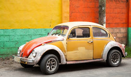 Old Mustard and Red Bug in Front of Colorful Wall Royalty Free Stock Photos