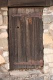 Old mystery wooden door. Old mystery rusty wooden door in stonewall Stock Images