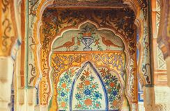 Old naive fresco with birds and floral patterns on historical home columns. SHEKHAWATI, INDIA - FEB 6, 2017: Old naive fresco with birds and floral patterns on Stock Images