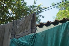 Old napkin and greenness bed sheet were dried in the sun stock image