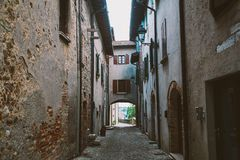 Old narrow alley in tuscan village - antique italian lane in Montalcino, Tuscany, Italy.  Stock Photography